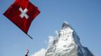 Schweizerfahne wird in die Luft geworfen, im Hintergrund das Matterhorn