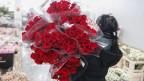 Frau mit schwarzen Haaren, die von hinten abgebildet ist, trägt mehrere Blumensträusse mit roten Rosen