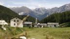 Blick auf eine Landschaft mit viel Wiese, Bergen und wenigen Häuschen