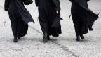 Drei Nonnen laufen über eine kopfsteingepflasterte Strasse.