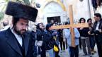 Im Vordergrund ist ein orthodoxer Jude sichtbar. Im Hintergrund steht eine Gruppe von Personen, von denen eine ein grosses hölzernes Kreuz trägt.