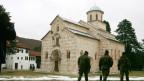 Vor dem Kloster Decani im Kosovo patroullieren Soldaten.