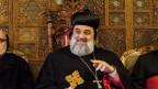 Bärtiger Mann in christlicher Kleinung sitzt auf einem verzierten Holzstuhl