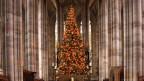 Ein beleuchteter und geschmückter Christbaum in einer Kirche