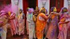Indische Witwen bemalen sich mit farbigem Puder.