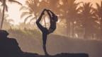 Eine Frau steht in der Dämmerung auf einem Felsen und praktiziert Yoga