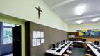 Ein Kreuz hängt in einem Schulzimmer.