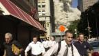 Foto von Menschen, die vor der Staubwolke des World Trade Center davonrennen.