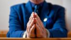 Gottesdienstbesucher faltet die Haende zum Gebet