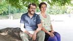 Camille Roseau und Christoph Good Roseau sitzen auf einem Stein.