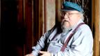 Ein älterer, etwas fülliger Mann mit Käppi sitzt auf einem hölzernen Thron.