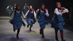Junge Frauen in blauen Kleidern gehen über eine Bühne