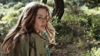 Eine junge Schauspielerin sitzt in einem Wald.