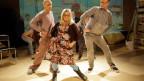 Zwei Männer und eine Frau auf der Bühne machen Tanzbewegungen.