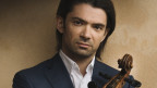 Ein Mann mit Geige blickt in die Kamera