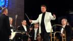 Dirigent mit weissem Jackett und Dirigentenstab steht auf der Bühne