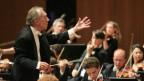 Dirigent um die 70ig-jährig dirigiert ein Orchester
