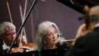 Frau mit grauen, langen Haaren sitzt am Klavier vor einem Orchester