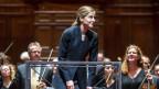 Dirigentin steht vor Orchester auf der Bühne
