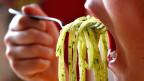 Geöffneter Mund mit einer Gabel Spaghetti mit Pesto davor.