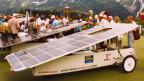 Ein Solarfahrzeug mit einem grossen Solarpanel als Dach wird von Zuschauern inspiziert.
