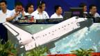 Chinesische Studenten vor dem Modell einer Rakete.