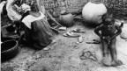 Ein Mädchen und seine Mutter nach einer Beschneidung in einem afrikanischen Dorf.