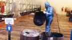 Nach dem Unglück: Ein Mitglied des Seuchenkommandos leert ausgebrannte Fässer in die bereitgestellten Abfallbehälter.