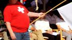 Mann mit Bauch im roten Oberteil mit CH-Flagge drauf.