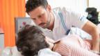 Ein Pfleger hilft einer Patientin.