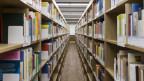 Ein Gang in einer UNiversitätsbibliothek mit Regalen, gefüllt mit unzähligen Büchern.