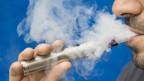 Eine Person mit einer E-Zigarette im Mund