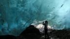 Person steht unterhalb eines Gletschers
