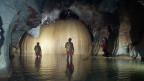 Höhlenforscher stehen in einem unterirdischen Fluss