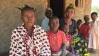 Eine junge Mutter aus Mozambik lacht in die Kamera