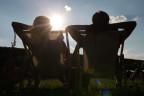 Zwei Menschen sitzen ruhig in der Sonne.