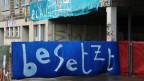 """Auf einem blauen Banner steht in weissen Lettern: """"besetzt""""."""
