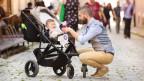 Ein Mann kniet nieder und blickt zu seinem Kind, das im Kinderwagen sitzt.