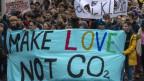 Eine Menge aus jungen Menschen läuft durch eine Strasse mit einem farbigen Transparent auf dem steht: Make Love not CO2.