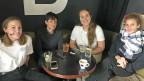 Vier Frauen sitzen an einem runden Tisch, darauf stehen Kaffeetassen - und es liegen vier Handys drauf.