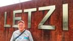 Ein Mann steht vor dem Stadion Letzigrund. Auf dem T-Shirt trägt er ein Einhorn.