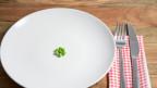 Ein Teller mit ein paar Erbsen