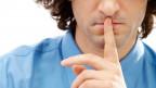 Mann mit Zeigefinger vor der Lippe