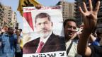 Die Proteste der Muslimbrüder flammen erneut auf. Ein ägyptischer Fan des gestürzten Präsidenten Mohammed Mursi hält ein Plakat von ihm in arabischer Schrift in Kairo, Ägypten, am 4. Oktober 2013.