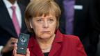 Die deutsche Bundeskanzlerin Angela Merkel präsentiert im März 2013 ein abhörsicheres Handy von Blackberry an einem Stand von Secusmart während der Computermesse CeBIT in Hannover expo.