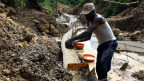 Ein kongolesischer Mann beim Goldschürfen in einem Fluss, der durch eine Goldmine in der Nähe der östlichen Stadt Kamituga, Kongo, fliesst.