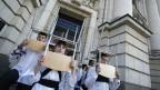 Eine Gruppe von bulgarischen Studenten tragen Stühle auf dem Kopf während einer Protestaktion vor der Universität Sofia in Sofia . Archivbild.