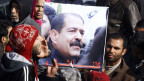 Tunesier halten ein Bild des ermordeten Oppositionspolitikers Chokri Belaïd während der Beerdigung.