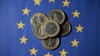 Ein-Euro-Münzen auf der EU-Flagge.