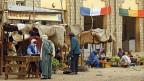 Eine Strasse in Timbuktu; eine französische und eine malische Flagge über zwei Haustüren.